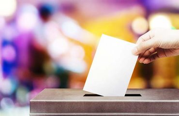 Colorful fo election vote, hand holding ballot paper for election vote concept at colorful background.