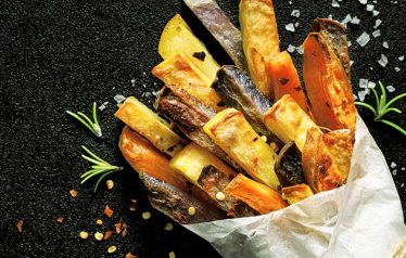 French fries,  baked fries from different types and colors of potatoes sprinkled with herbs and spices in paper bag on a black background, top view, copy space